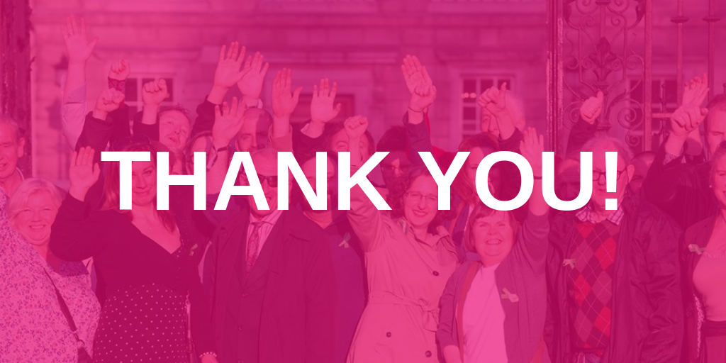 "Image of group of people outside of Dáil Éireann with their hands in the air. The image has a pink wash over it with text reading ""THANK YOU!"" in the centre written in white font."